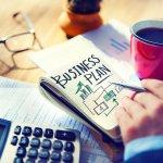 mão masculina com uma caderneta escrita business plan. Ao lado uma calculadora e uma xícara de café. Imagem ilustrativa texto plano de negócios franqueadora