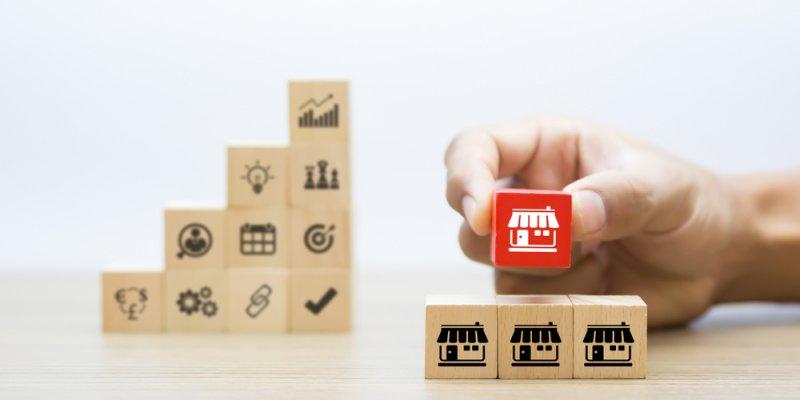 blocos com desenhos variados ligados a empreendimentos ao fundo. Em primeiro plano 4 blocos : três na base com simbolo de loja e um no topo em vermelho com o mesmo desenho. Imagem ilustrativa texto ABF
