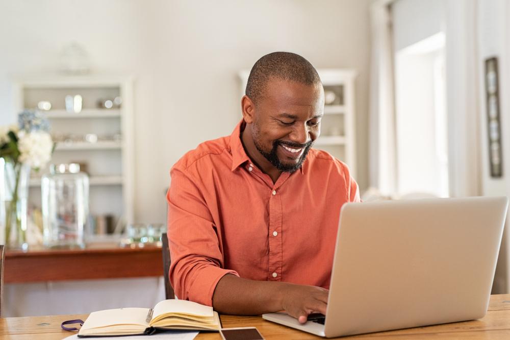 Vemos um homem mexendo no computador com um caderninho ao lado (imagem ilustrativa). Texto: cliente oculto franquias.
