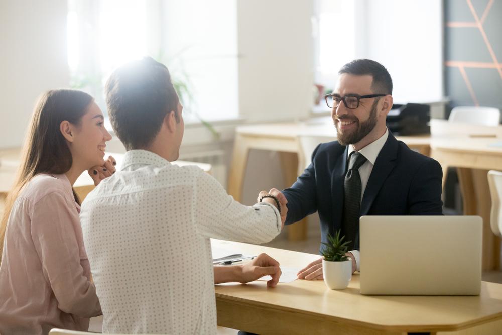 Vemos um casal (homem e mulher) conversar com um representante comercial de uma marca. Sorrindo, a mulher vê o seu parceiro apertar a mão do representante simbolizando o fechamento de um negócio (imagem ilustrativa). Texto: como investir em uma franquia.