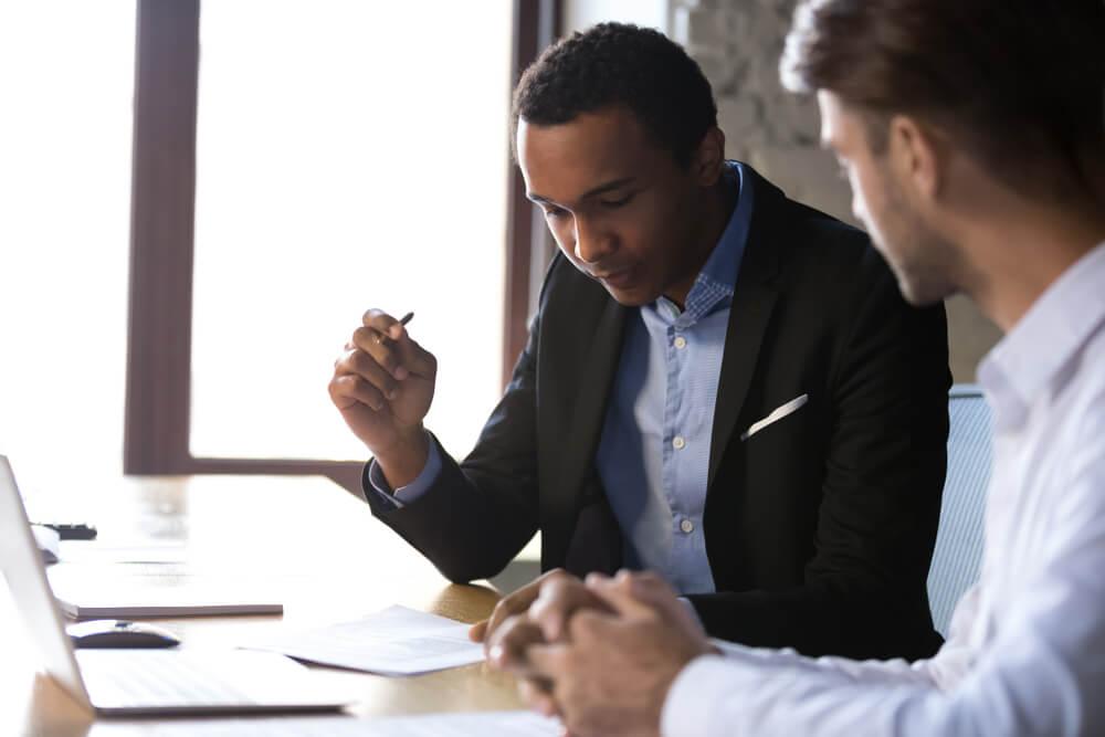 Dois homens conversam e analisam um documento (imagem ilustrativa). Texto: como investir em uma franquia.