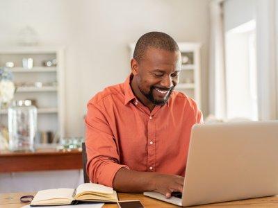 Homem trabalhando em frente ao computador e em casa. Imagem ilustrativa texto como trabalhar home office
