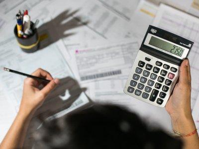 moça usando calculadora e com um lápis na mão, com a foto tirada de cima imagem ilustrativa do texto sobre crédito para abrir empresas