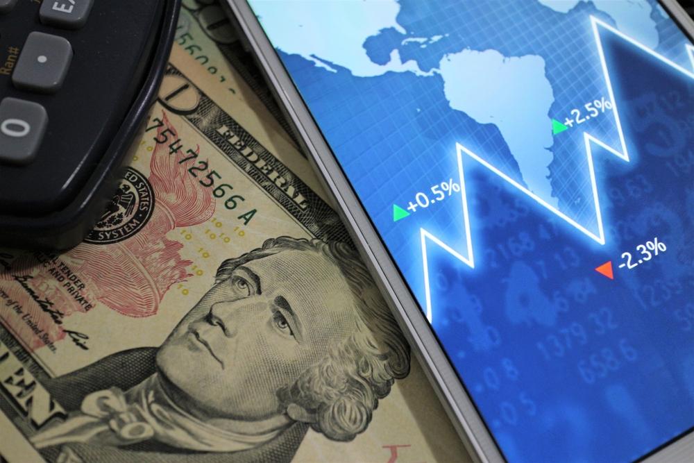 Celular com gráfico sob notas de dólares e calculadora ao lado. Imagem ilustrativa texto encontre sua franquia