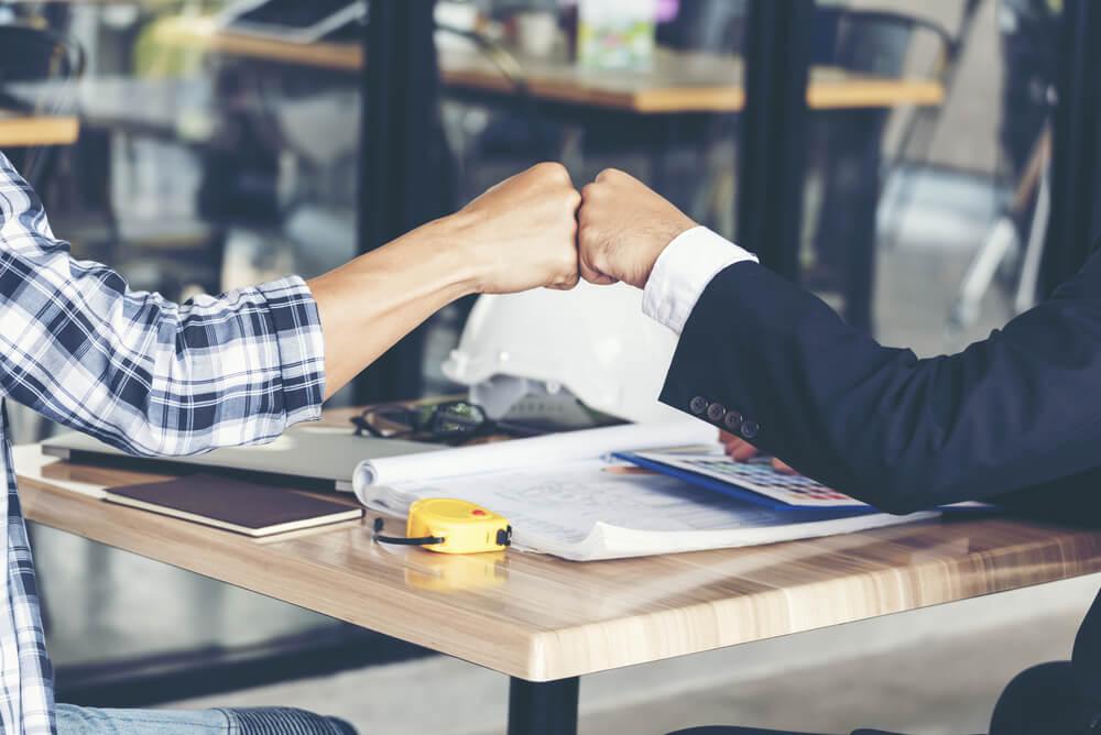 É possível notar que são dois homens. Sentados à mesa, com computador, trema, cadernetas de anotação, calculadora e outros objetos, eles se cumprimentam com um toque de punhos cerrados. A princípio, parece-nos que eles finalizaram um planejamento.