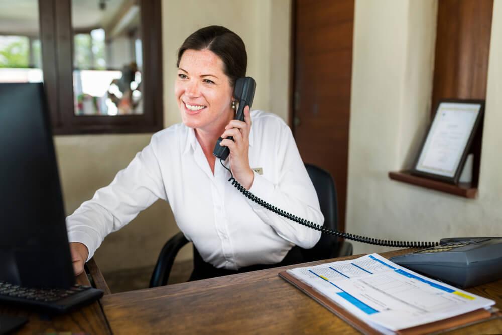 Vemos uma mulher em um escritório conversar ao telefone enquanto realiza uma consultar no seu computador com uma planilha de documentos a frente (imagem ilustrativa). Texto: etapas de franquias.