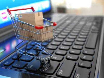 Pequeno carrinho de supermercado sobre um computador e com algumas caixas dentro. Imagem ilustrativa texto fornecedores franchising