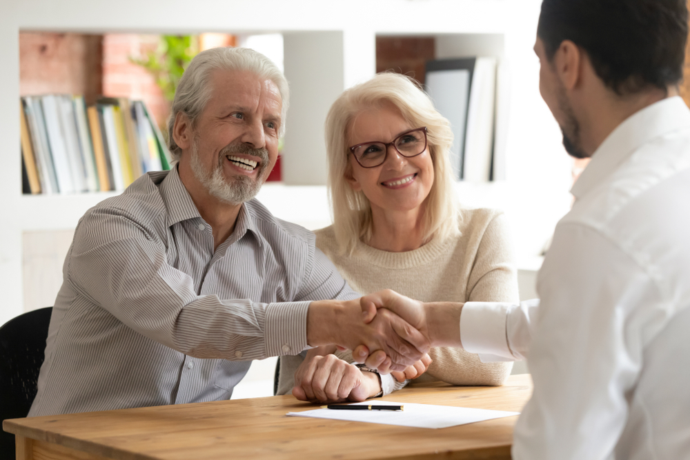 Casal com cabelos grisalhos apertando a mão de um empresário após assinar um documento.