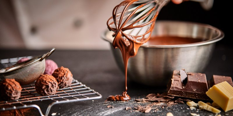 Padeiro ou chocolatier preparando bombons de chocolate batendo o chocolate derretido com um batedor pingando no balcão abaixo. Imagem ilustrativa texto franquia cacau show