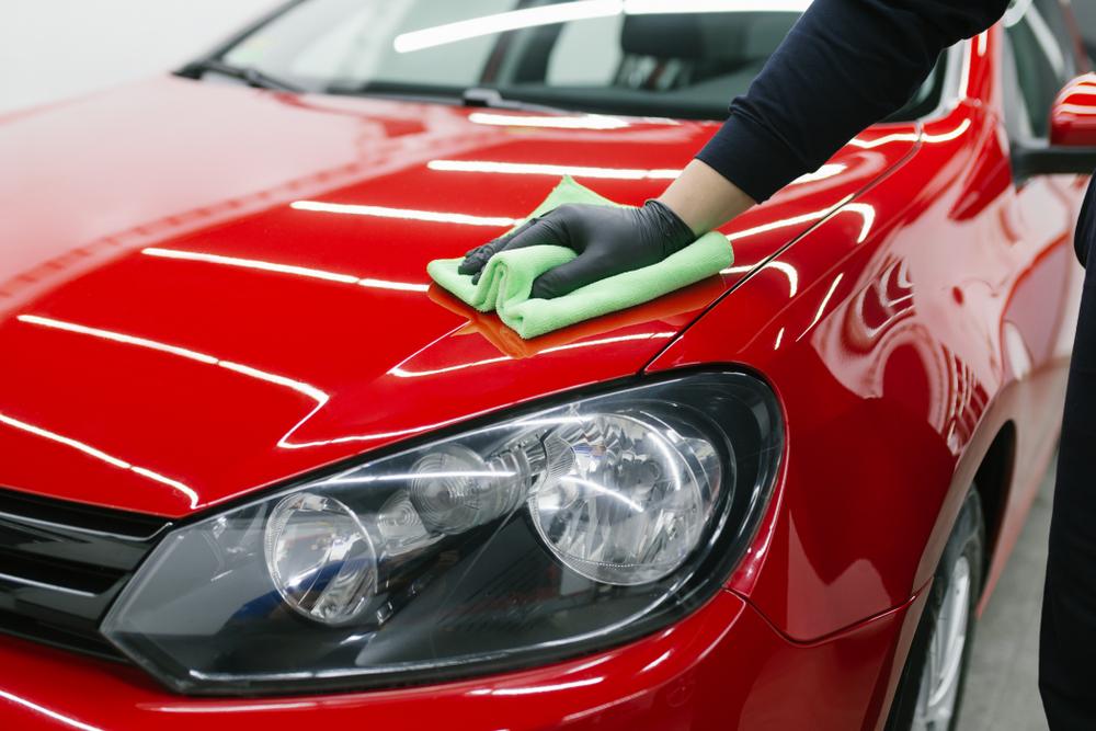 homem passando flanela sobre o capo de um carro vermelho. Imagem ilustrativa texto franquia de automóveis