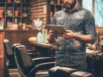 homem mexendo no tablet em sua barbearia. Imagem ilustrativa texto franquia de barbearia