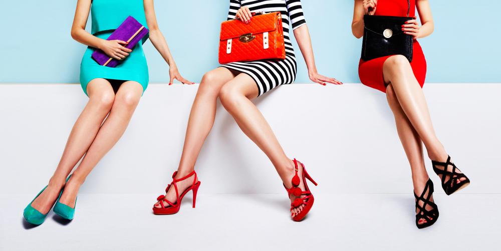 Vemos três mulheres sentadas em um banco branco expondo seus saltos para propaganda (imagem ilustrativa). Texto: franquia de sapatos.