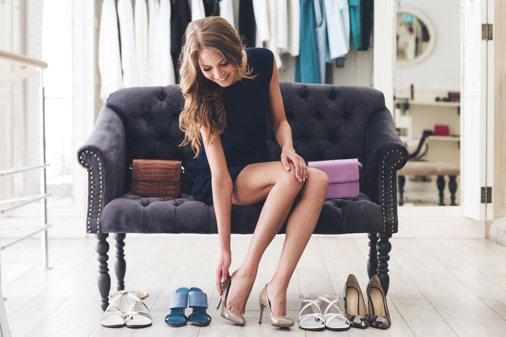 Vemos uma mulher em uma poltrona calçando um salto com outras peças ao lado (imagem ilustrativa). Texto: franquia de sapatos.