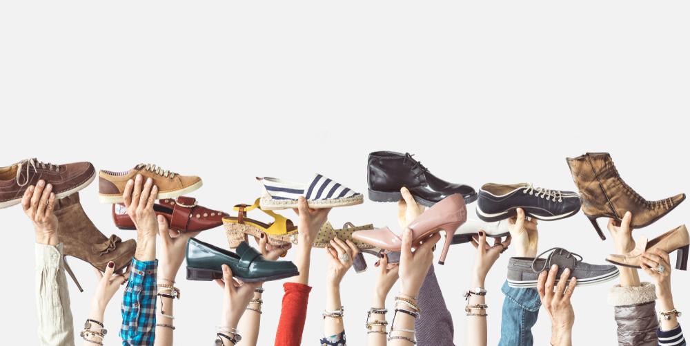 Mãos com diversos calçados erguendo-os (imagem ilustrativa). Texto: franquia de sapatos.