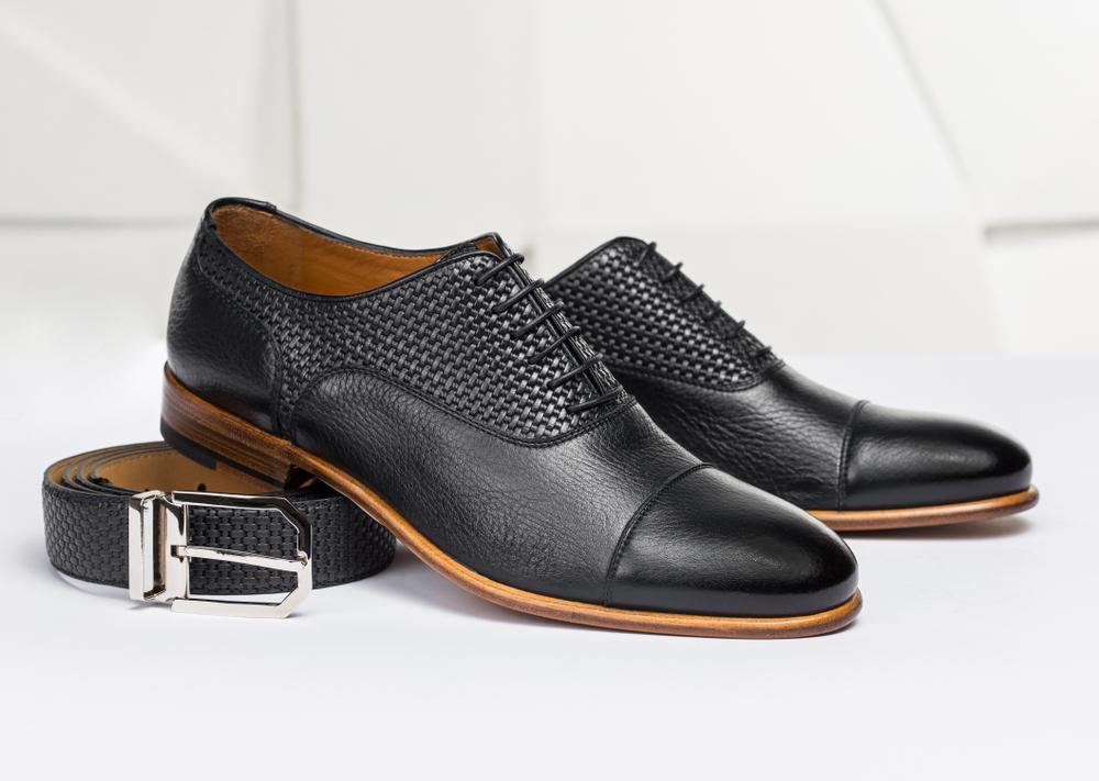 Sapato masculino sobre um cinto masculino. Ambos de couro