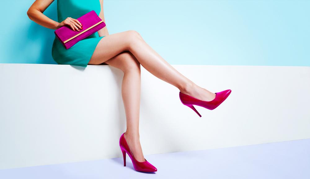 Vemos uma mulher sentada sobre um banco na cor branco com um salto rosa combinando com a bolsa.