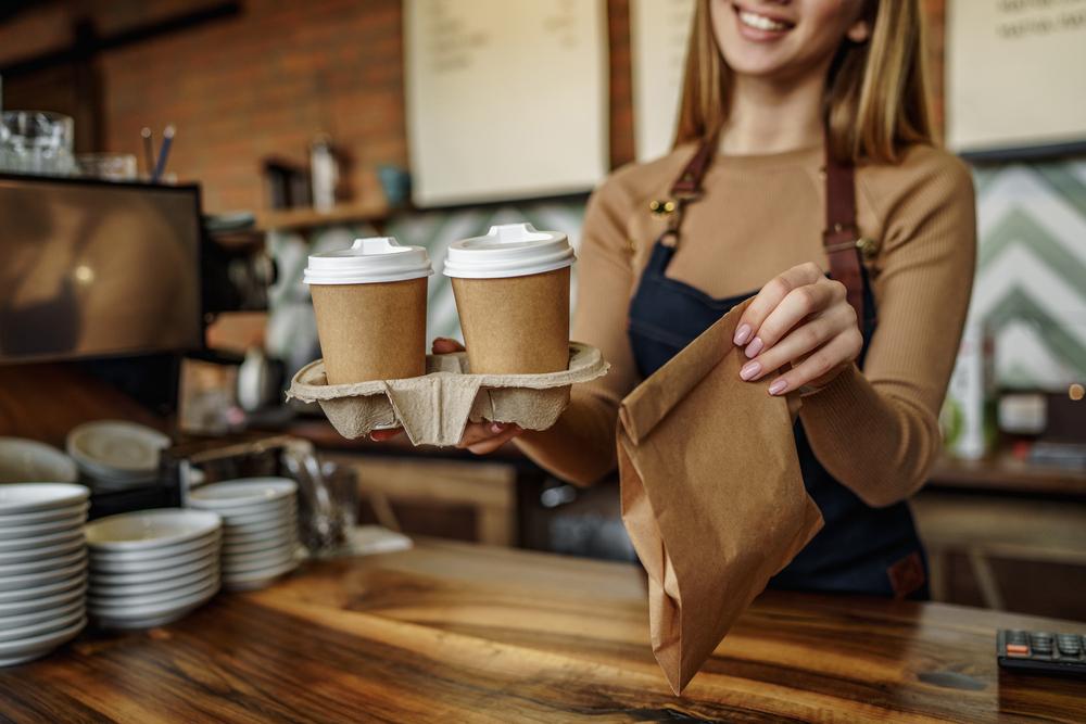 Vemos uma barista trabalhando em uma cafeteria (imagem ilustrativa). Texto: franquia doce.