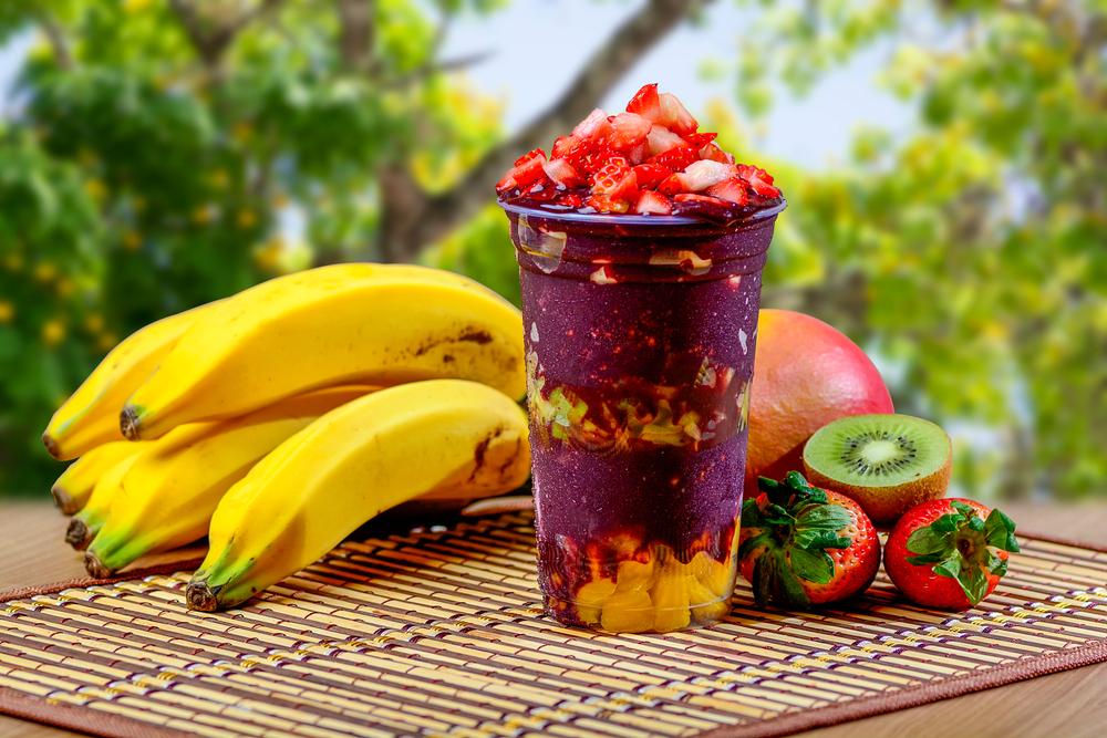 Copo de açaí exposto com frutas como banana, morango e kiwi (imagem ilustrativa). Texto: franquia doce.
