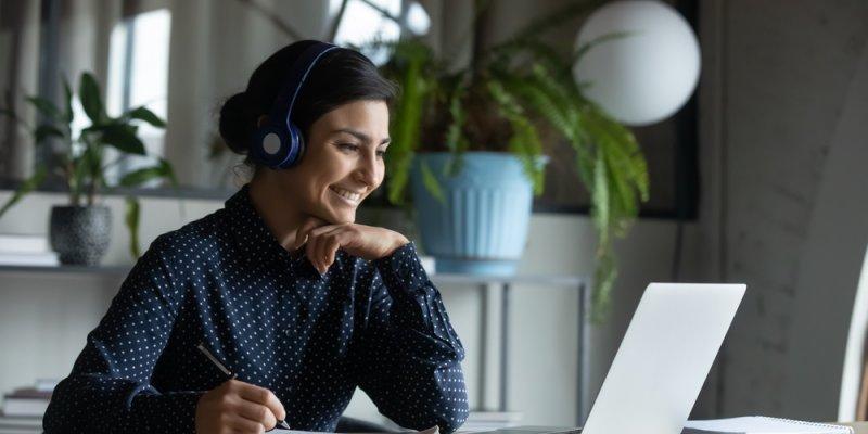 Jovem feliz com fones de ouvido sem fio, olhando para a tela do laptop. Imagem ilustrativa texto franquia qualifica cursos