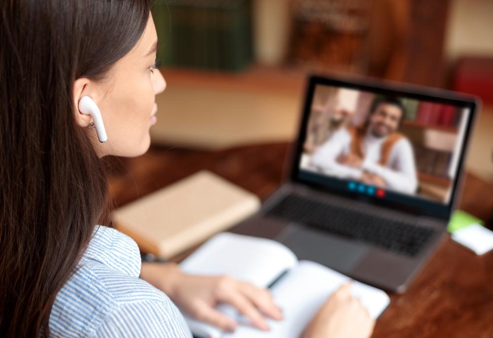 Vemos uma jovem mulher com fones de ouvido em uma videoconferência com seu professor; Ela está em uma mesa e, enquanto presta atenção no professor, ela realiza algumas anotações. Os dois parecem discutir o material de estudo (imagem ilustrativa). Texto: franquia qualifica cursos.