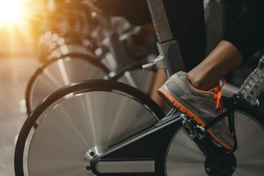 Vemos uma série de bicicletas de academia alinhadas enquanto várias pessoas praticam esse exercício (imagem ilustrativa). Texto: franquia Velocity.