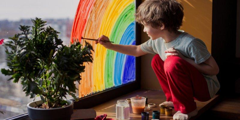 criança pintando arco-iris na janela. Imagem ilustrativa texto franquia youplay