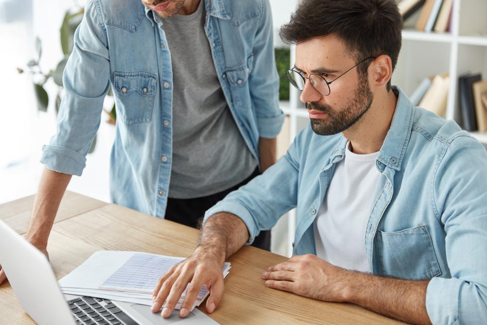 Homem mexendo no computador com outra pessoa ao lado (imagem ilustrativa). Texto: franquias 15 mil.