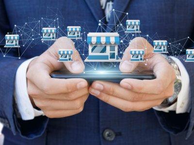 Homem mexendo no celular e algumas lojas ao desenhadas ao lado. Imagem ilustrativa texto franquias curiosas