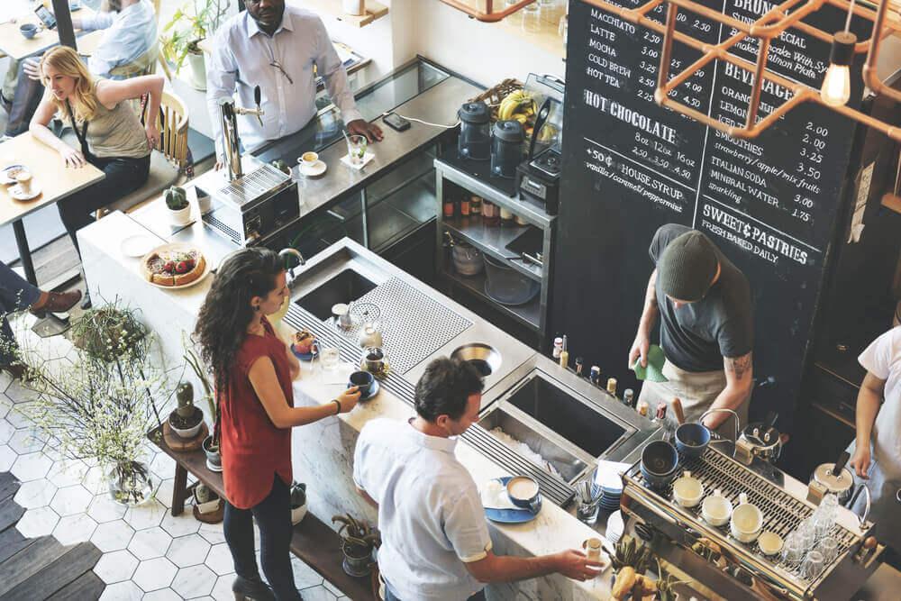 Imagem de uma cafeteria em movimento com clientes e operadores (imagem ilustrativa). Texto: franquias de café.