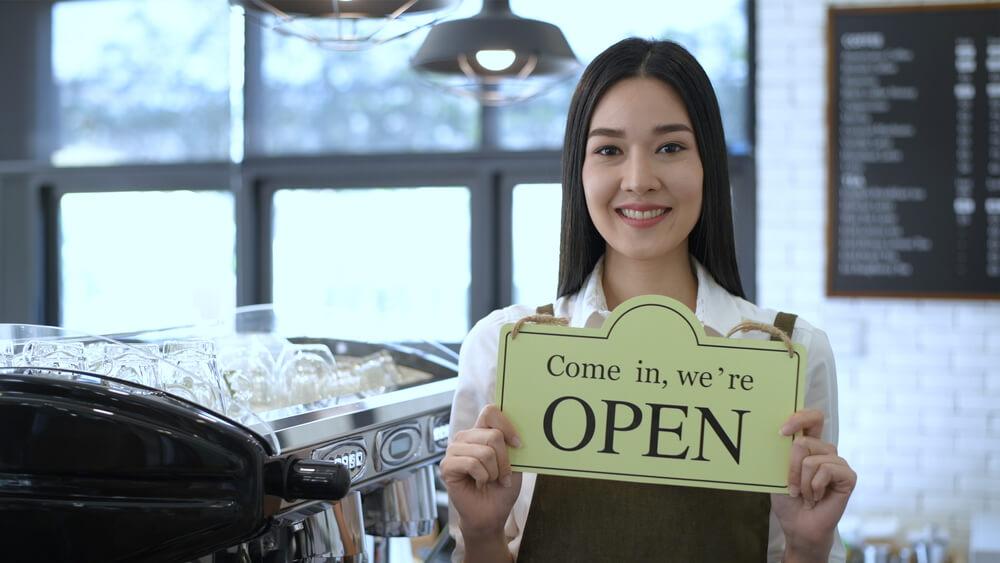 """Vemos uma mulher segurar placa escrito """"Venha, estamos abertos"""" uma cafeteria (imagem ilustrativa). Texto: franquias de café."""