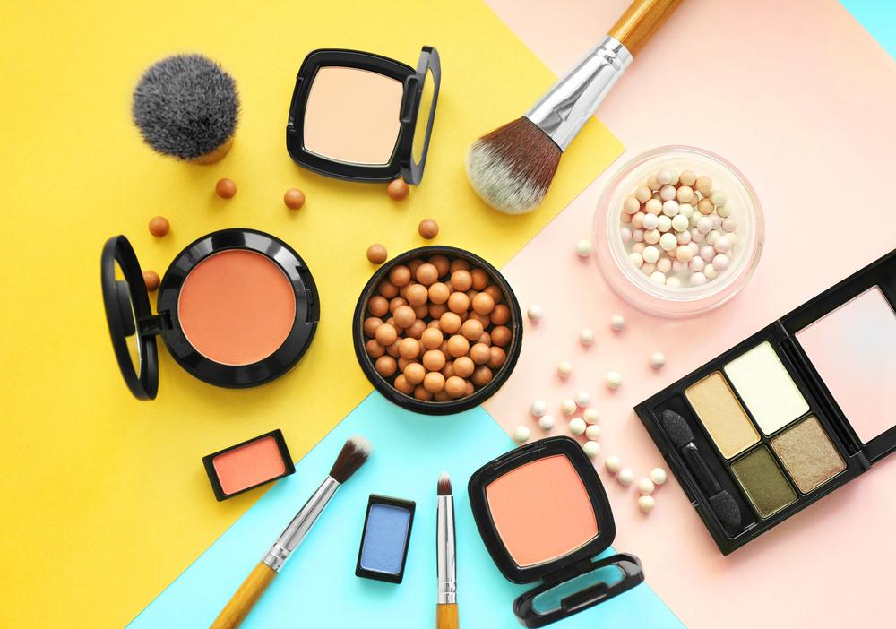 Vemos vários produtos de maquiagem sobre folhas coloridas diversas (imagem ilustrativa). Texto: franquias de cosmético.