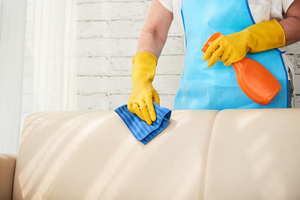 Foto de uma pessoa com avental azul e luva amarela segurando uma flanela azul e borrifador laranja para limpar sofá bege. Ao fundo temos uma parede branca.