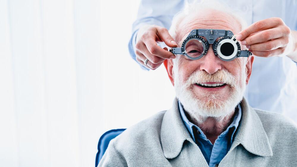 Vemos um senhor sendo atendido por um oftalmologista (imagem ilustrativa). Texto: franquias saúde.