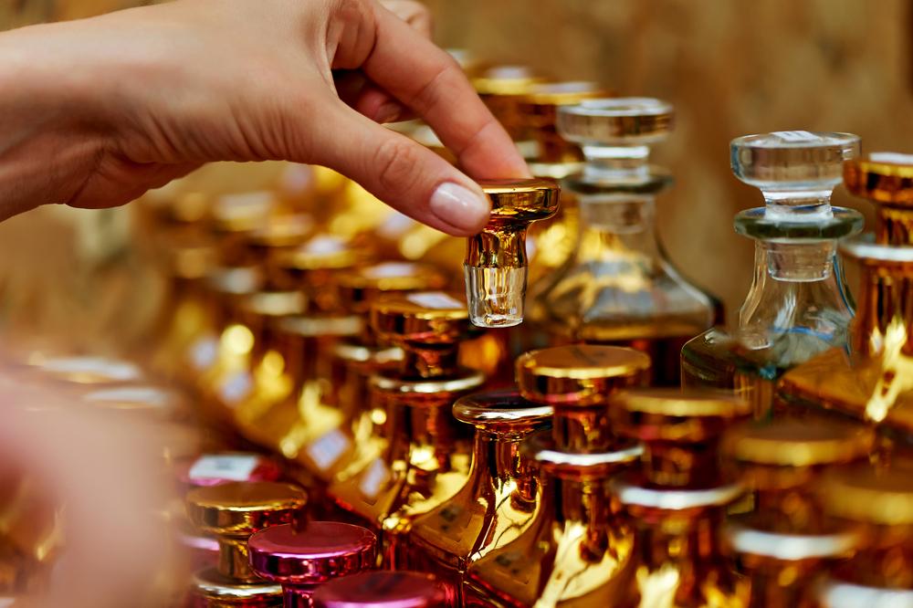 Vemos alguns perfumes expostos numa bancada (imagem ilustrativa). Texto: maiores franquias do mundo.
