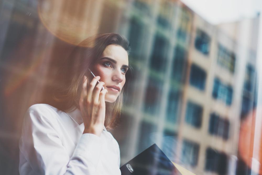Vemos uma mulher conversando ao telefone atrás de uma janela de vidro enquanto olha fixamente para a frente (imagem ilustrativa).