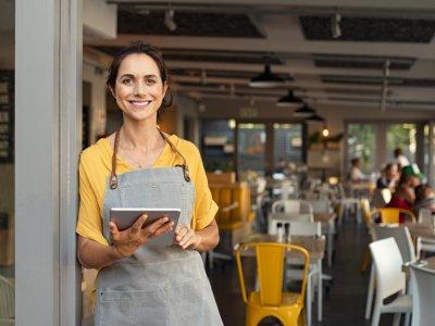 mulher em frente a uma loja com tablet na mão. Imagem ilustrativa texto passos abrir franquia