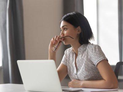 Mulher em frente ao computador com óculos na mão e com fisionomia de quem está pensando em algo. Imagem ilustrativa texto ser próprio chefe