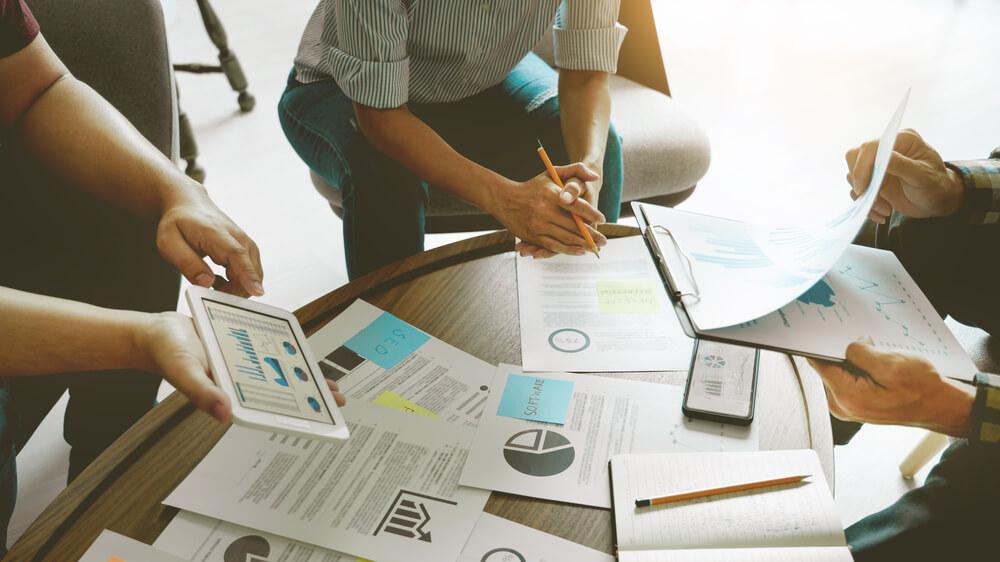 Pessoas reunidas com documentos e gráficos sobre a mesa (imagem ilustrativa). Texto: ser próprio chefe.