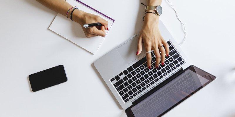 homem usando notebook e escrevendo em papel, em foto tirada de cima imagem ilustrativa texto trabalhar pela internet