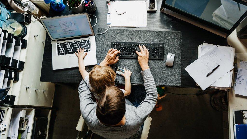homem trabalhando em home office com o filho no colo