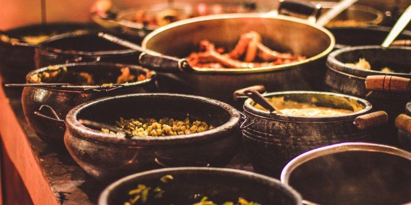 Comida brasileira em panelas de pedra sobre um fogão de lenha. Imagem ilustrativa texto franquia Griletto