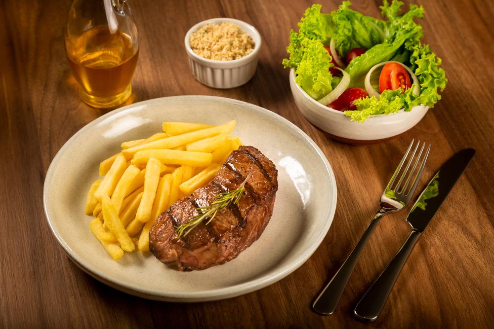 Vemos um prato de fritas com filé, acompanhado de salada e farofa em compartimentos separados (imagem ilustrativa). Texto: franquia Griletto.