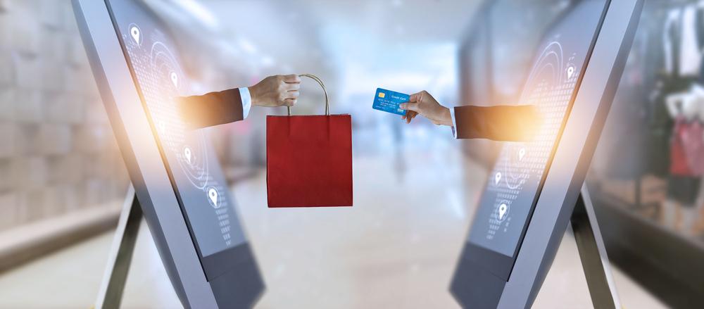 Vemos duas mãos saindo das telas de dois computadores. Uma delas entrega uma sacola enquanto a outra passa passa um cartão de crédito para o outro lado (imagem ilustrativa). Texto: franquia waybiz.