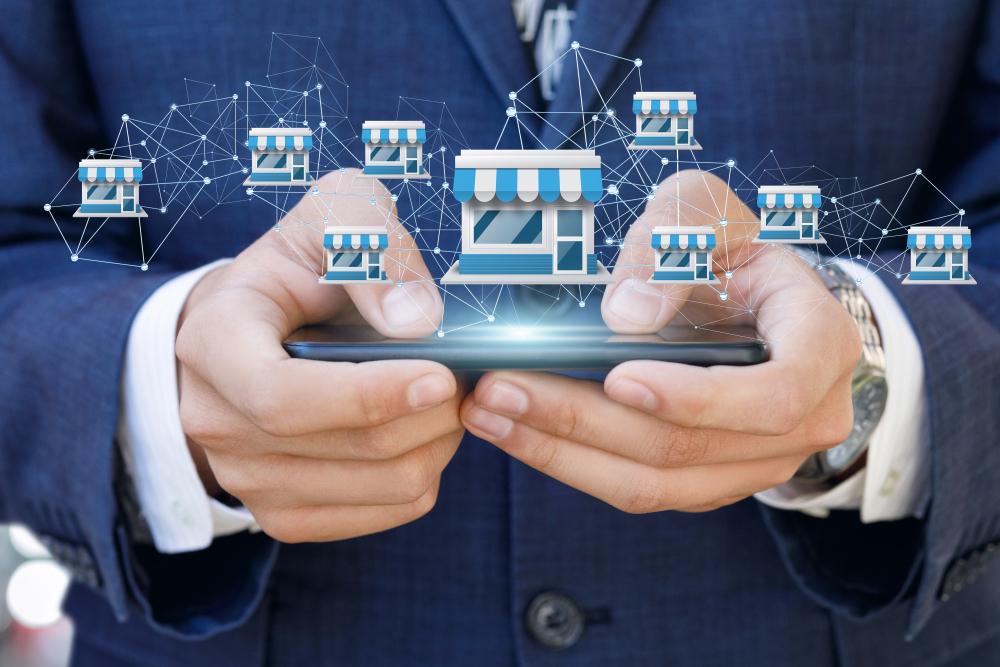 Vemos que um homem está mexendo no celular enquanto uma ilustração de lojas conectadas pairam sobre a tela (imagem ilustrativa).