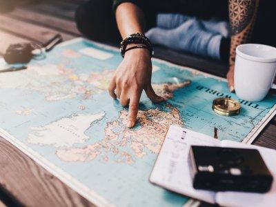 Mão feminina apontado para o mapa dos Estados Unidos com xícara ao lado e uma câmera fotográfica. Imagem ilustrativa texto franquias de turismo