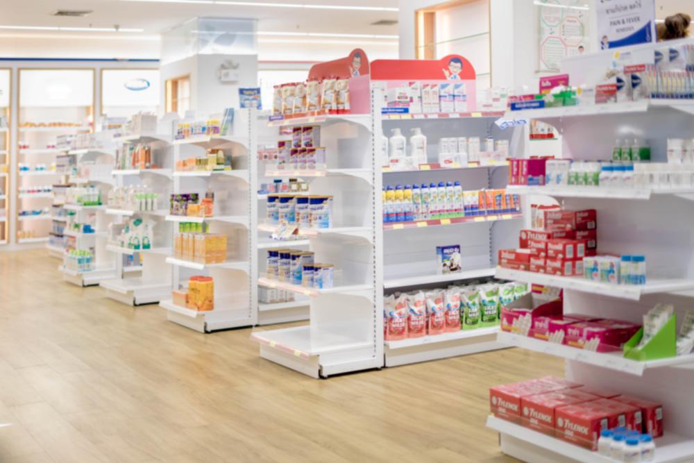 Vemos o interior de uma farmácia com produtos expostos nas prateleiras e seus corredores (imagem ilustrativa). Texto: franquias farmácias.