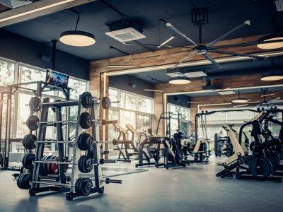 Imagem de uma academia com pesos e equipamentos. Imagem ilustrativa texto franquias fitness