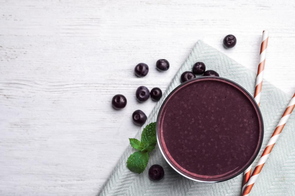 Vemos um copo com vitamina de açaí com alguns frutos de açaí ao lado (imagem ilustrativa). Texto: franquias fitness