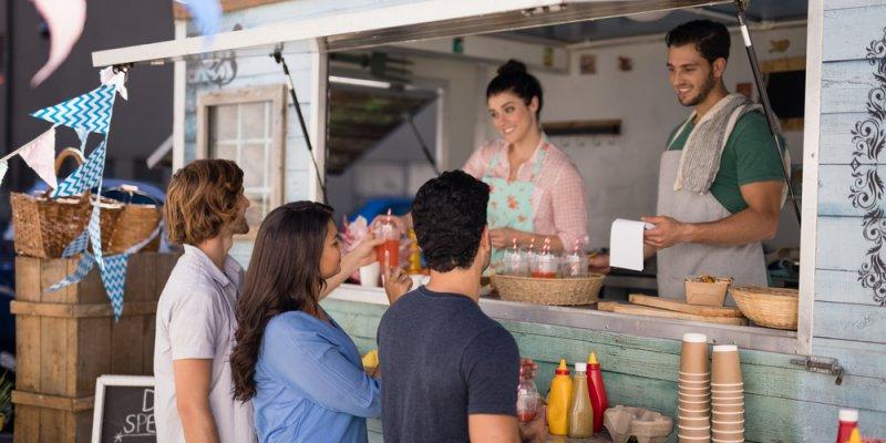Garçom sorridente tomando ordem do cliente no balcão no food truck. Imagem ilustrativa texto franquias food truck