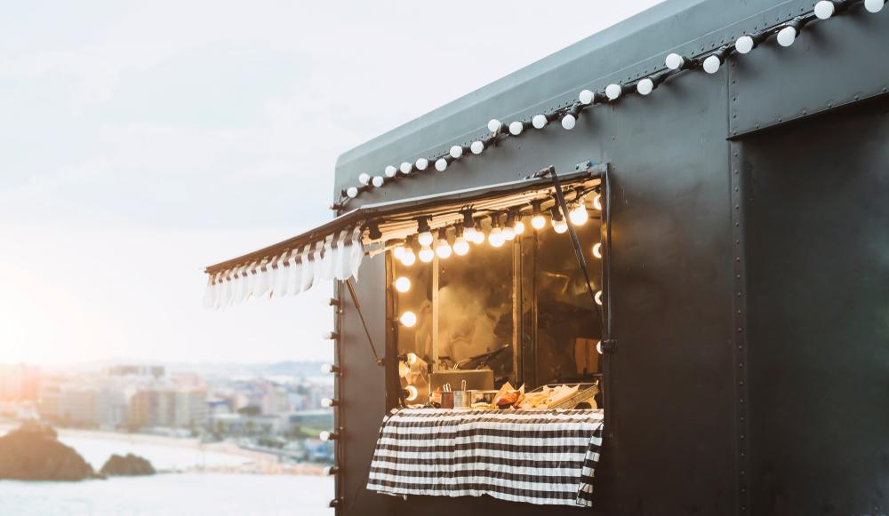 Food truck preto em uma praça aberta com vista da cidade ao fundo.